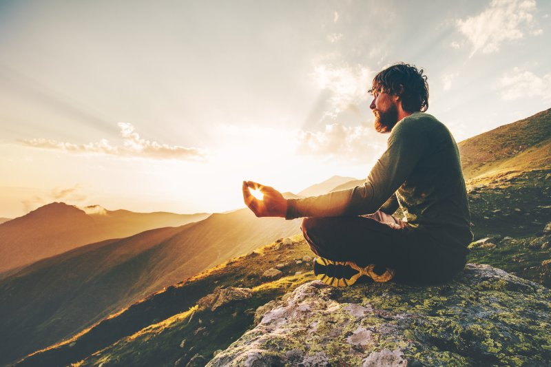 Muž meditující v přírode