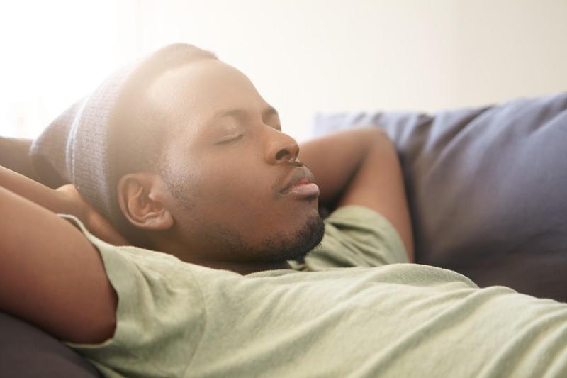 Muž spící na gauči.